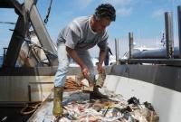 Pescador separa os peixes do lixo plástico que veio junto